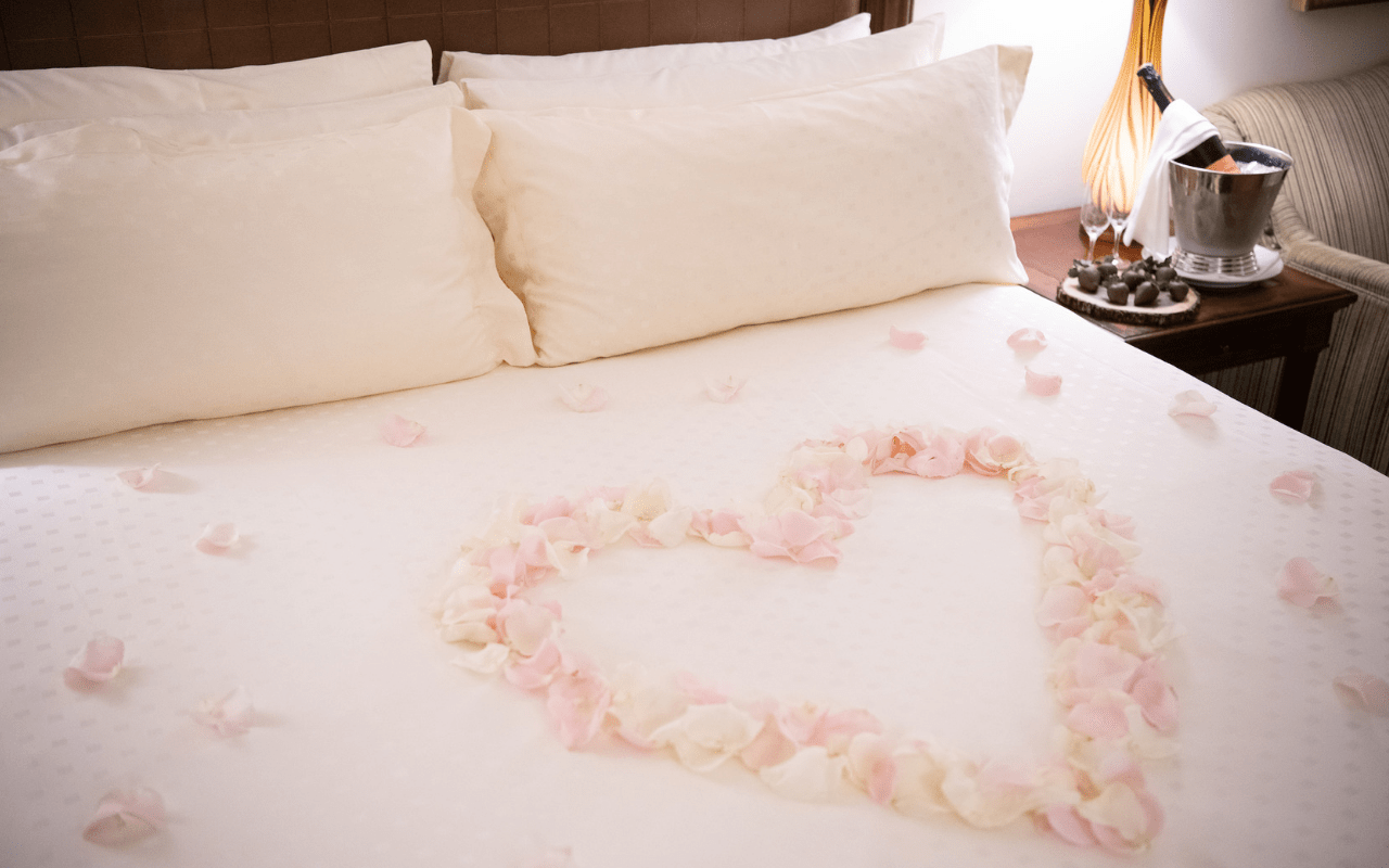 bed with rose petal heart, chocolates, and Champagne