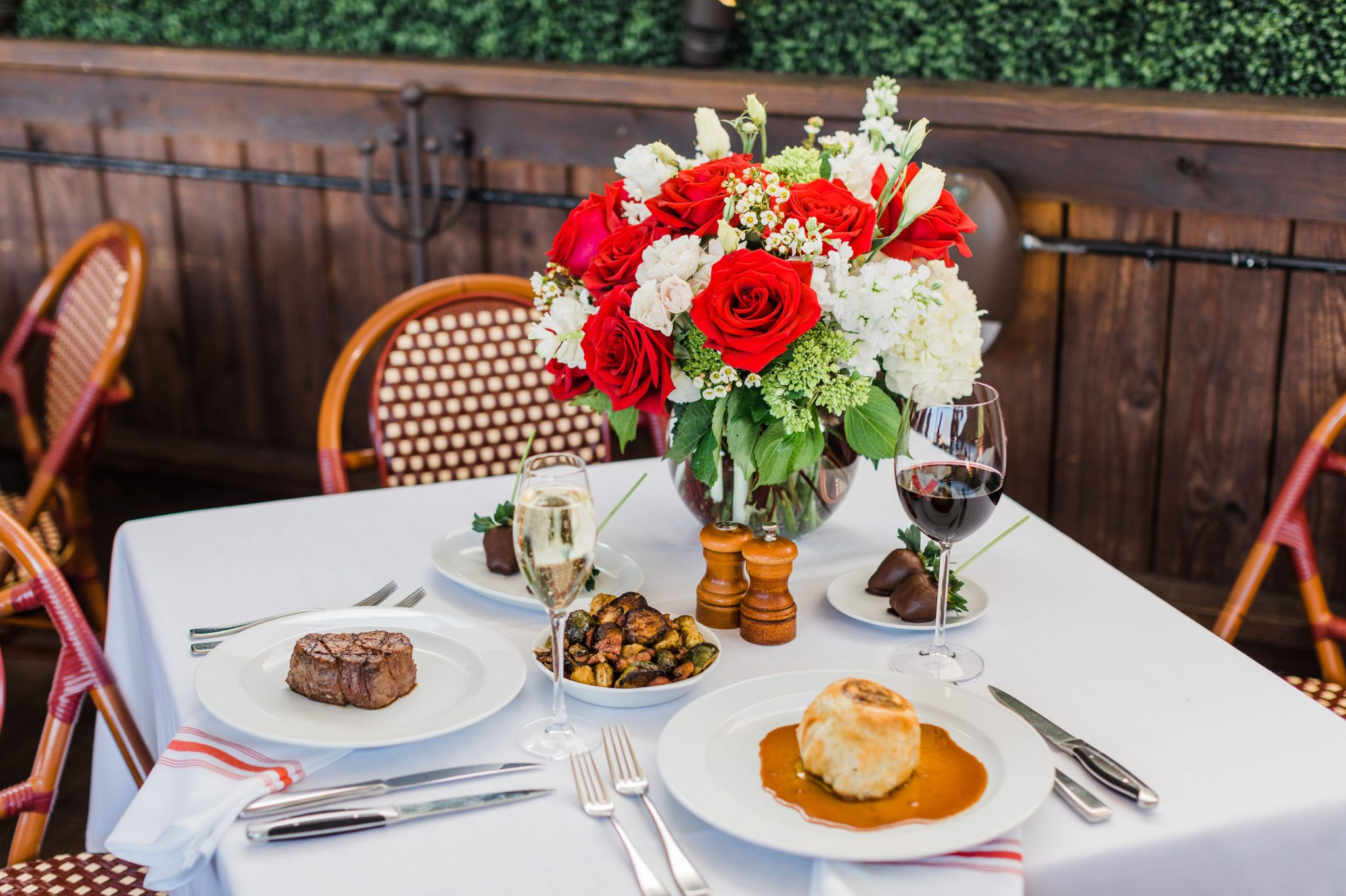 Picture of a table with seating for two, a steak at one place and a huge red and a huge red and a huge red and white floral arrangement.