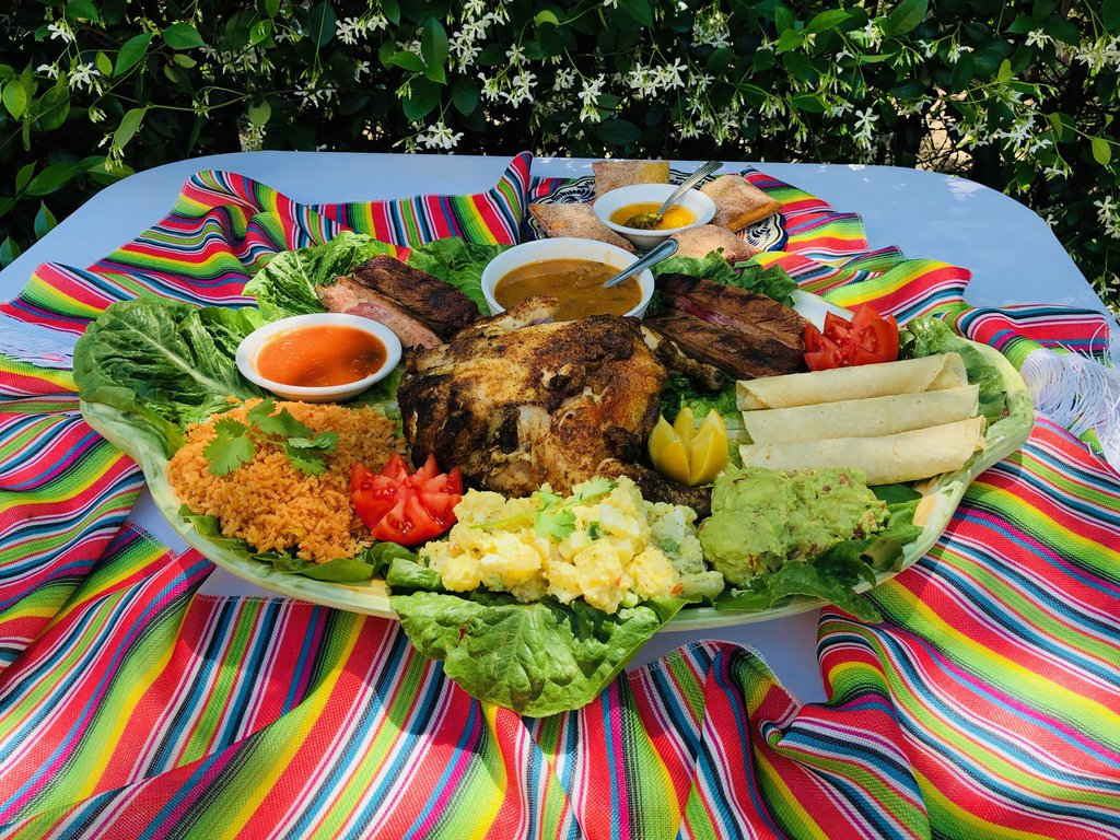 Photo of a whole chicken, Mexican rice and sauces on a striped blanket.