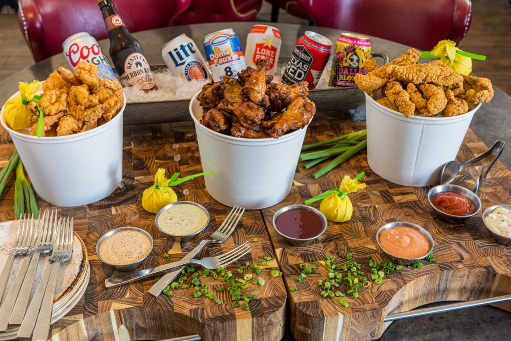 Photo of buckets of fried chicken and catfish, along with several sauces and beers
