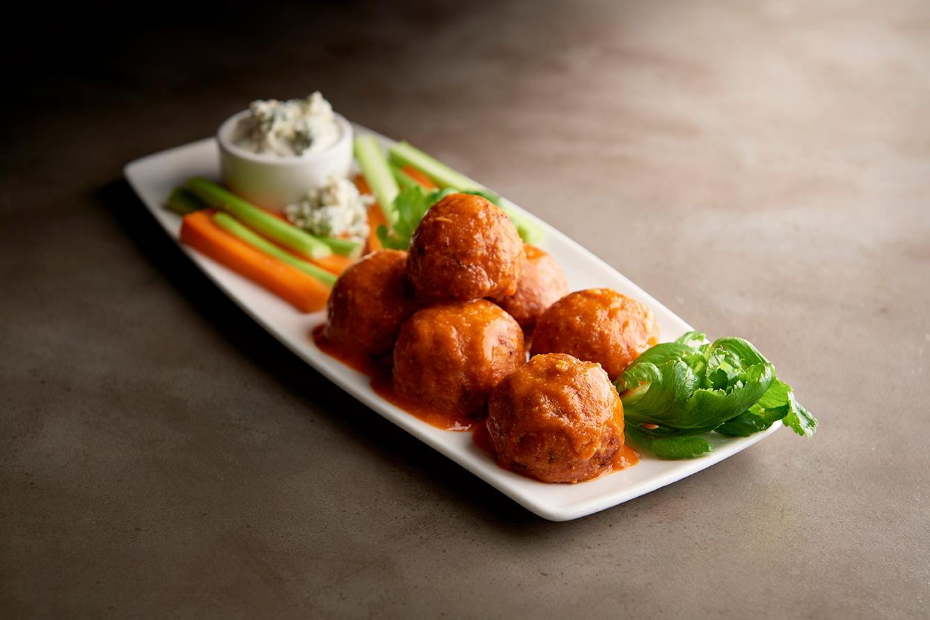 Photo of a plate of Buffalo chicken meatballs accompanied by celery and carrots and dip