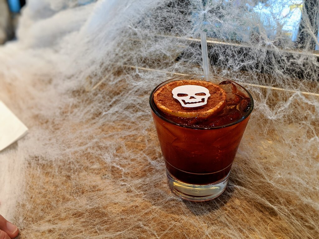 Picture of the Haunted Graveyard cocktail at Brennan's of Houston. It's dark amber with a skull on top of an orange for garnish.