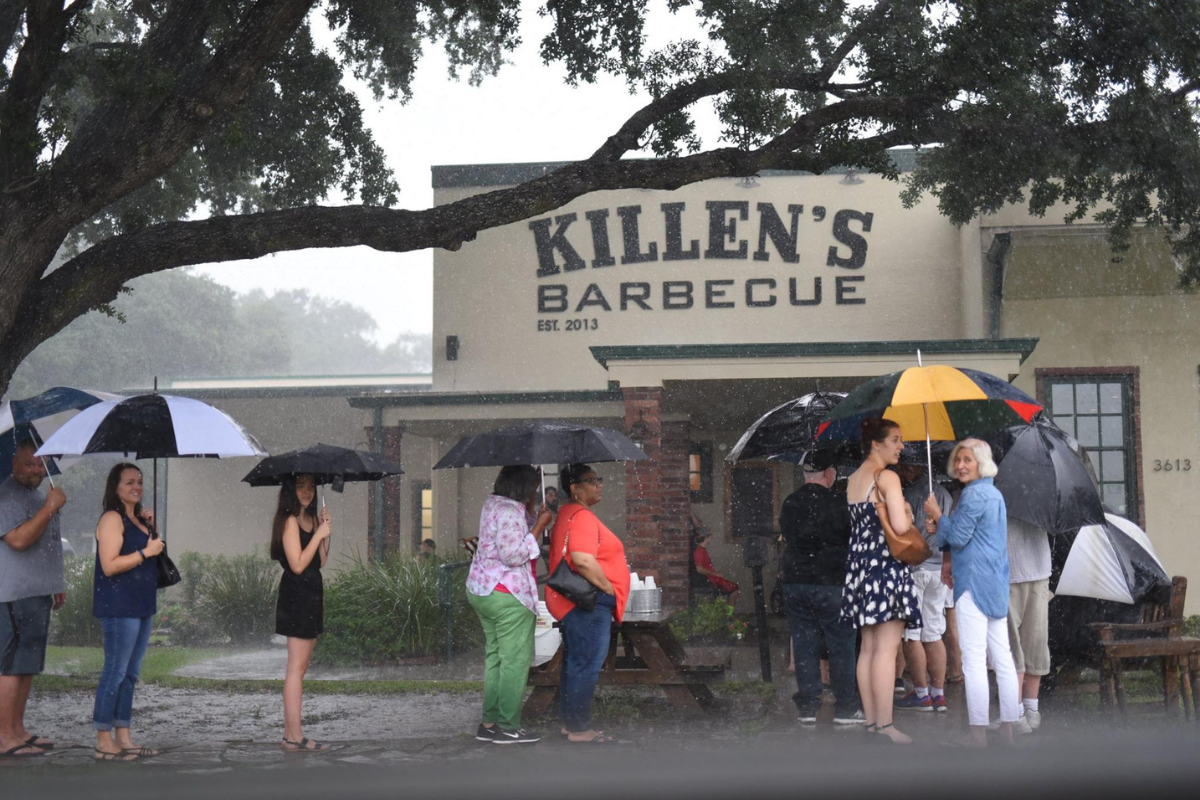 Customers wait in the rain in line at restaurant