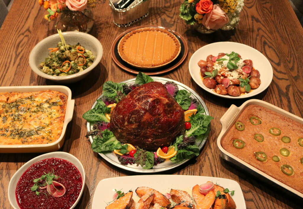 Photo of The Family Feast, centered by a spiral ham, surrounded by side dishes