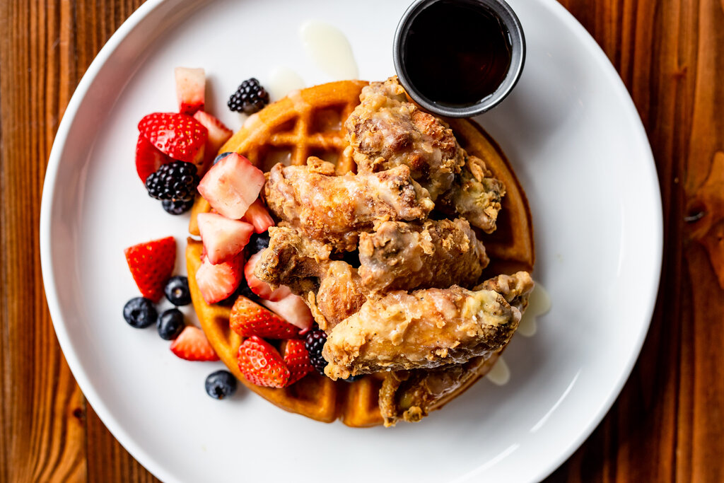 Photo of a plate of waffles topped with fried chicken wings