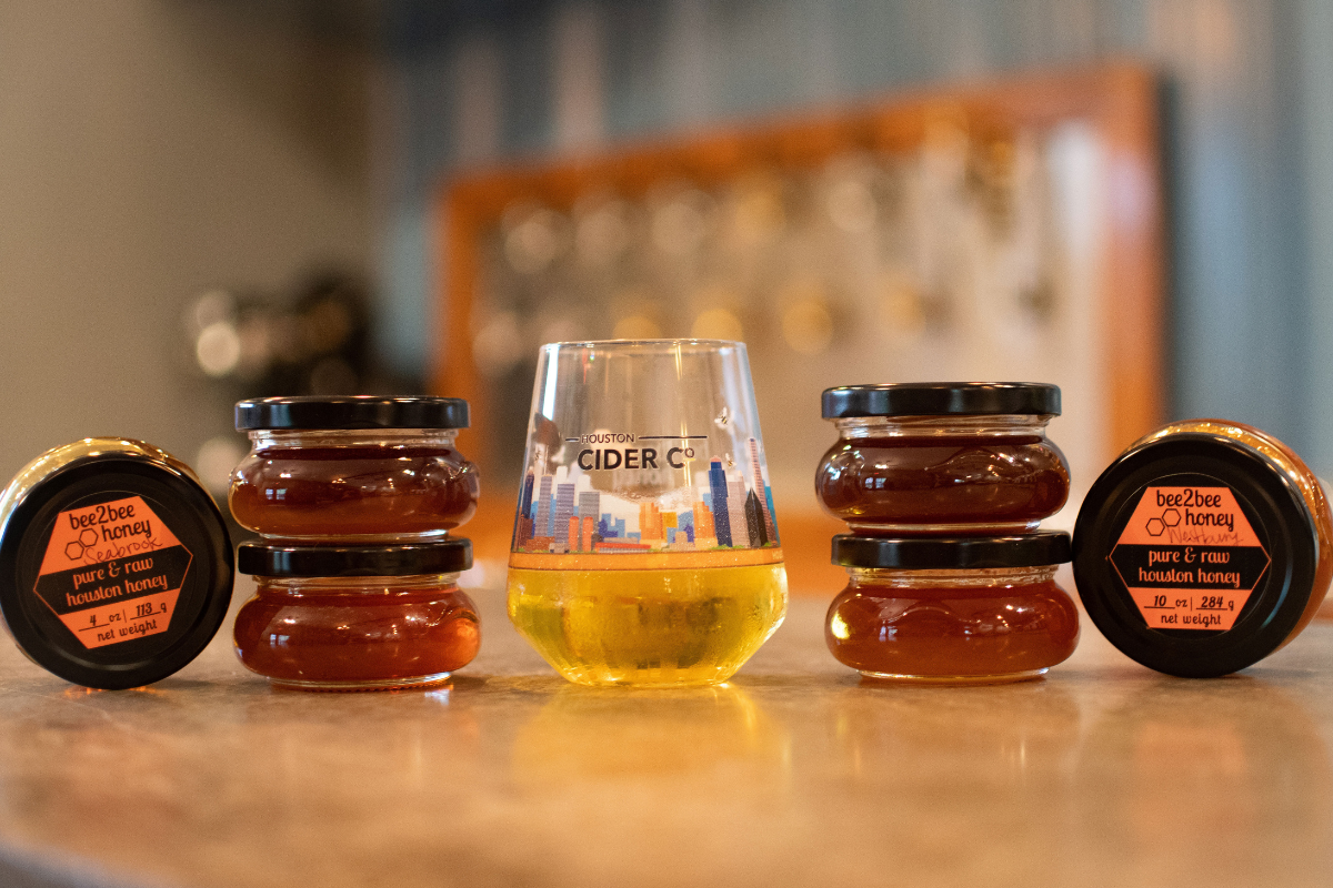 glass of cider flanked by stacked jars of honey