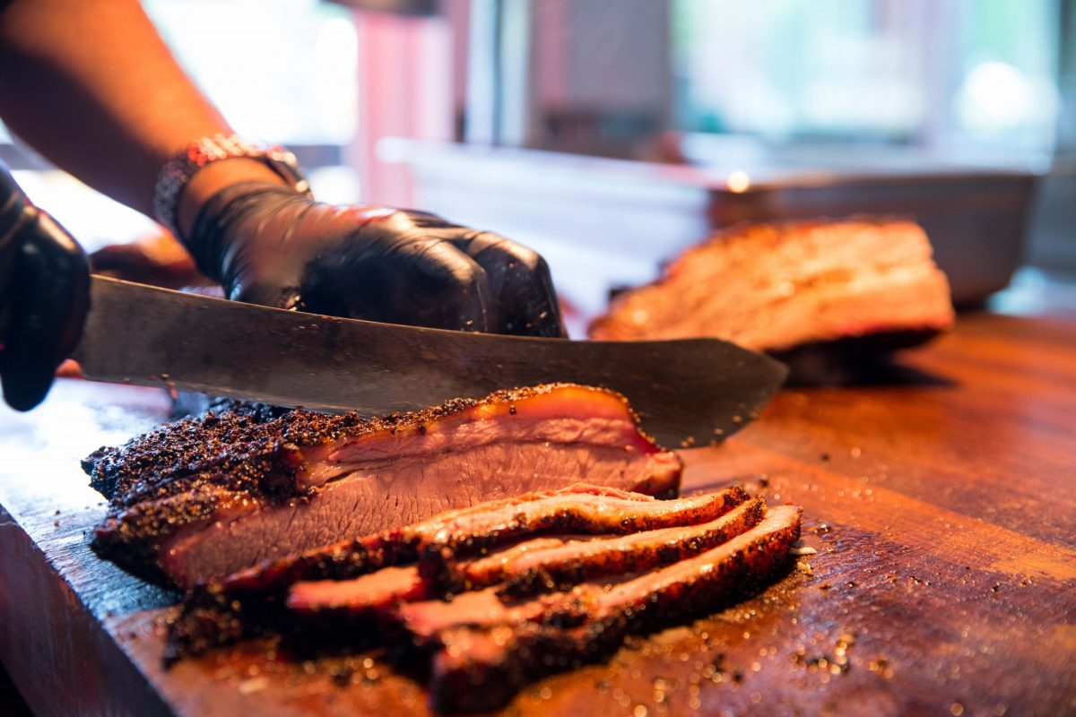 Photo of a brisket on a cutting board being carved