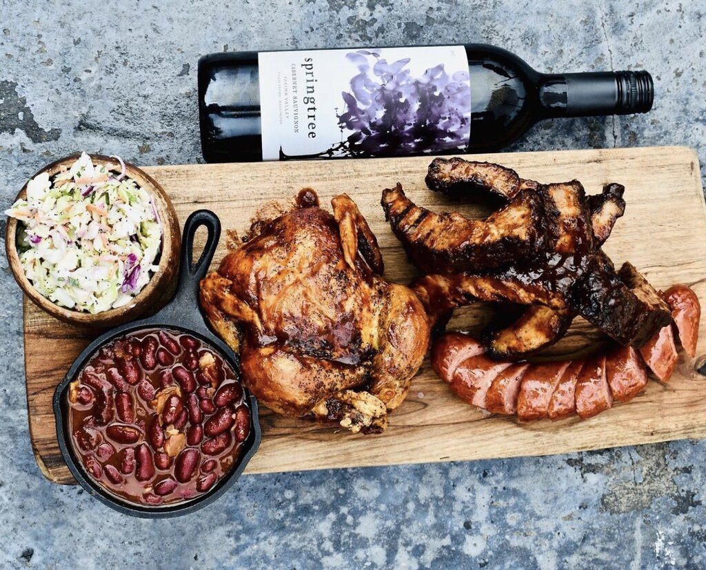 Photo of barbecue meats on a cutting board with a bottle of wine.