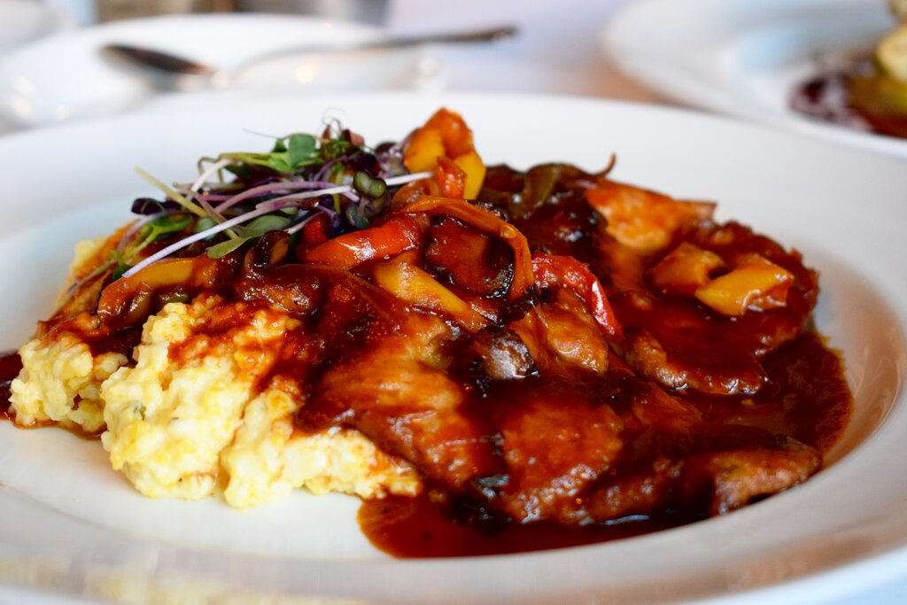 Plate of pork atop creamy goat cheese grits