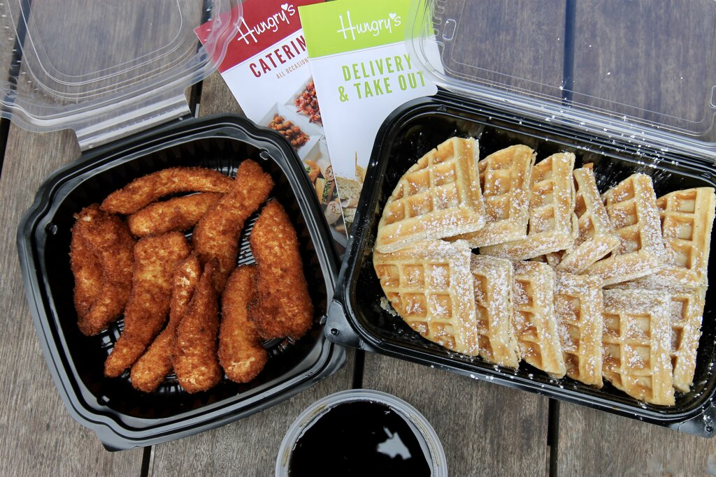Photo of to-go containers of fried chicken and waffles