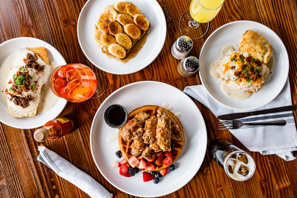 Several dishes of brunch options including wings and waffles and biscuits and gravy.