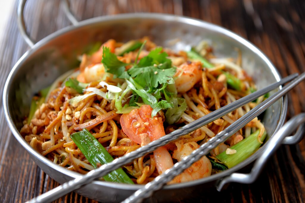 Picture of a shallow metal pan filled with noodles and greens.