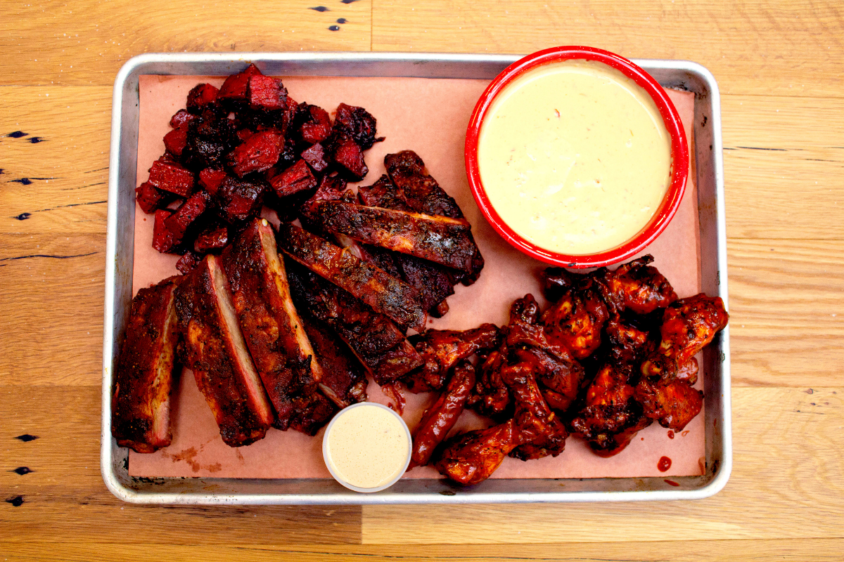 plate of barbecue wings, ribs and burnt ends with queso