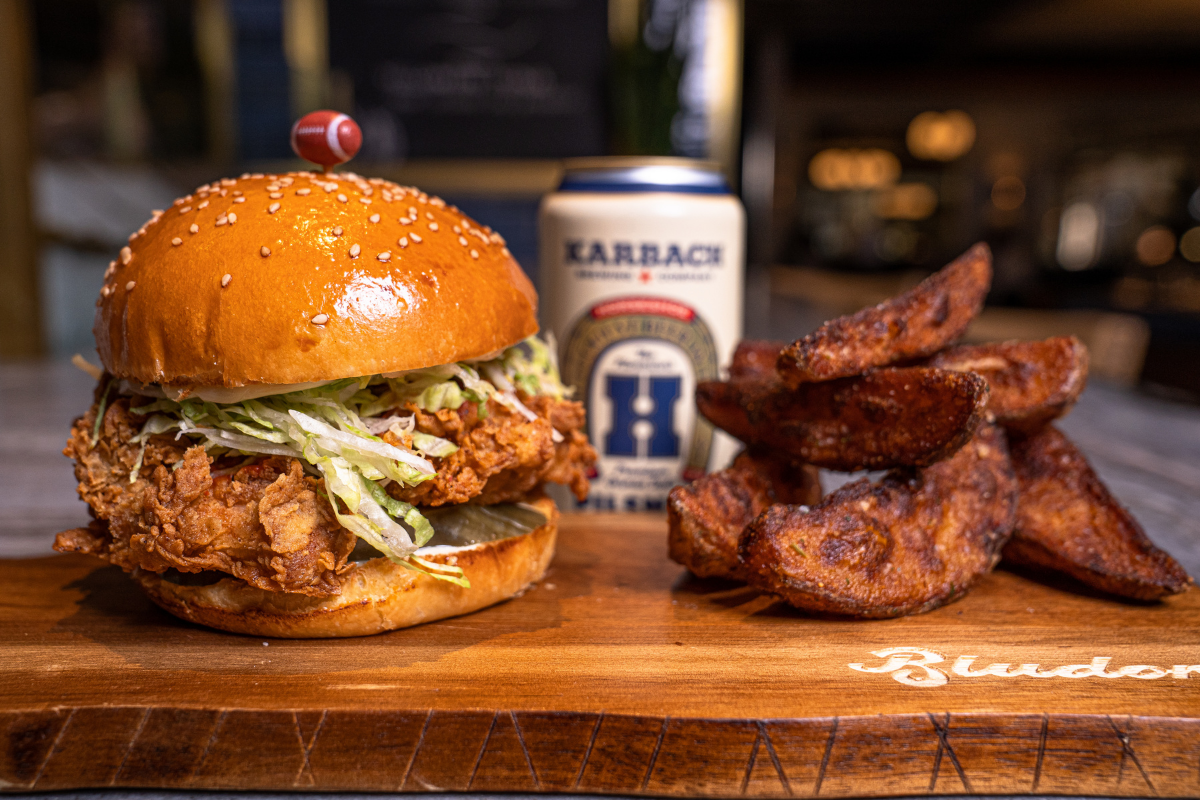 Fried chicken sandwich, can of beer, potato wedges