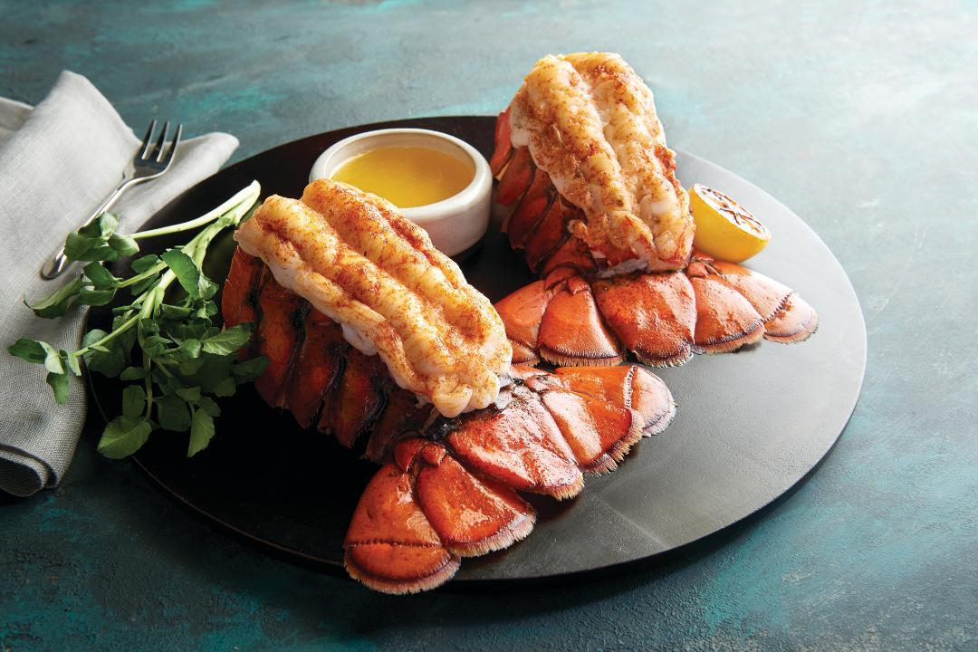 Picture of two lobster tails on a plate with drawn butter