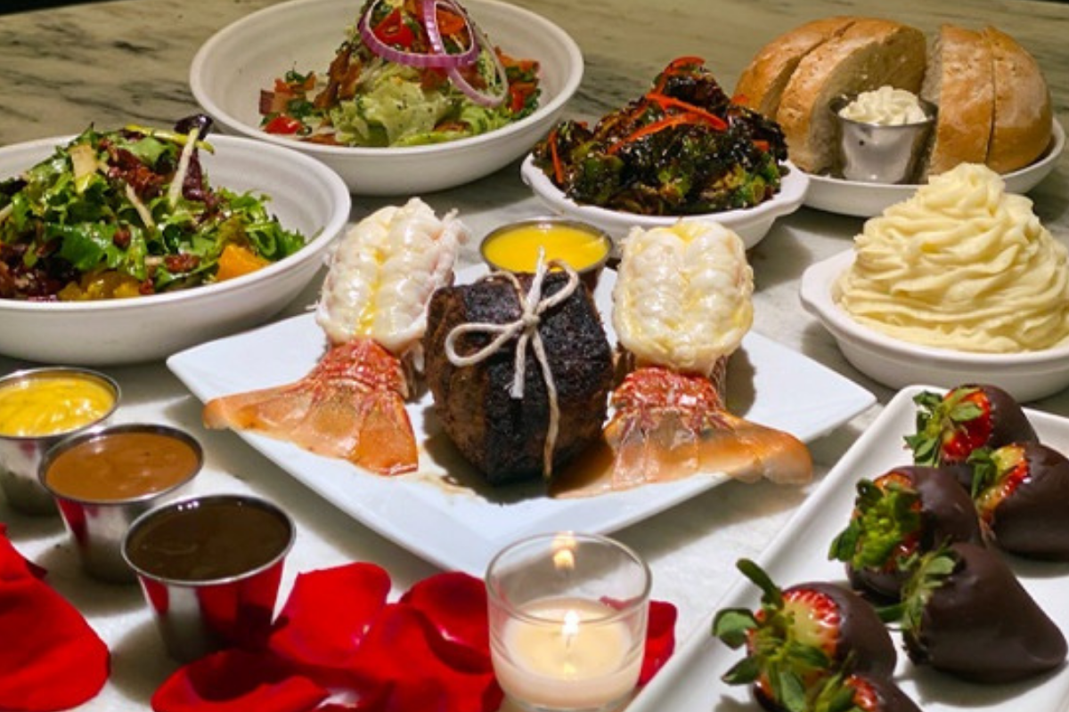 Picture of a filet with two lobster tails, salad, potatoes, rose petals and a candle