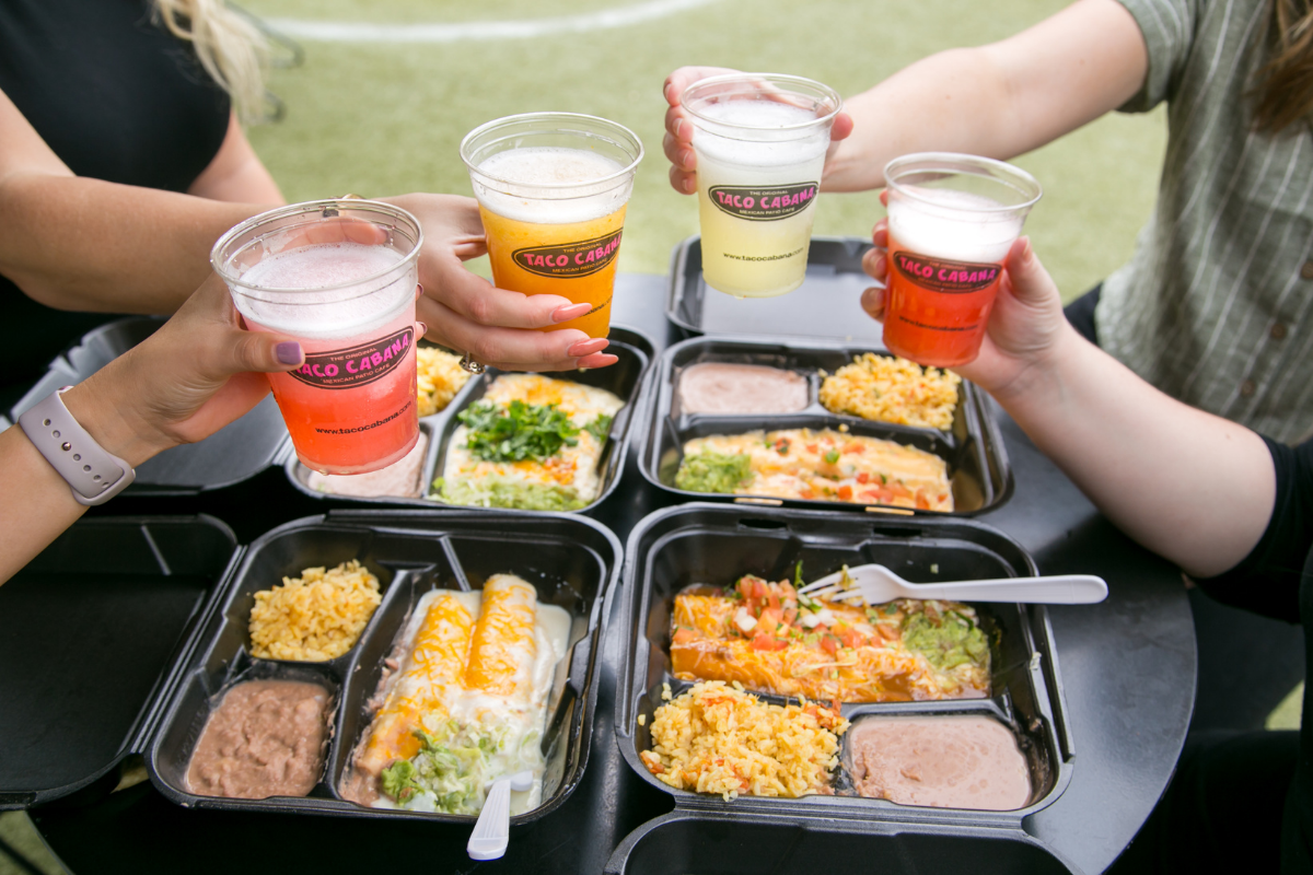 to-go plates of tex-mex food and people holding margaritas