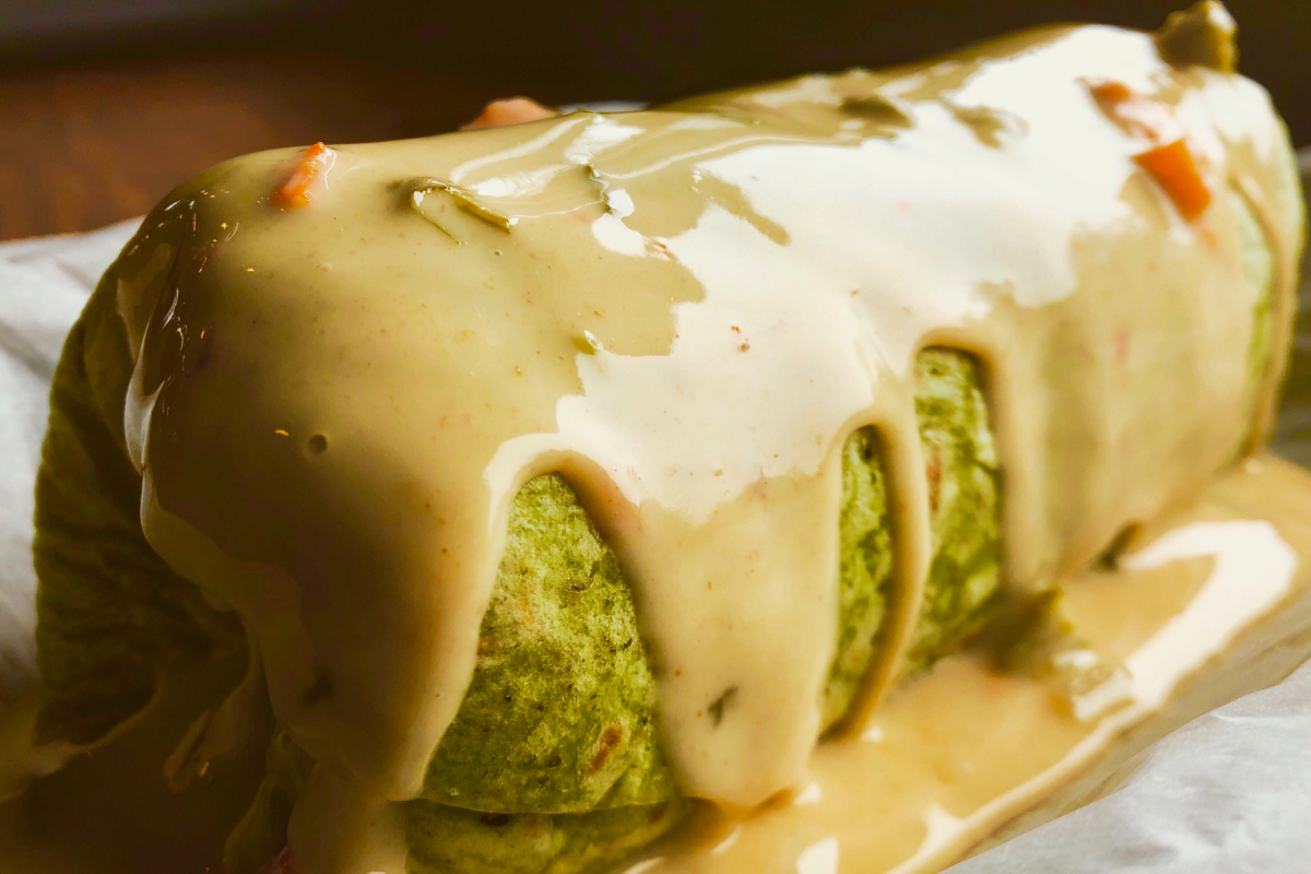 green burrito covered in queso