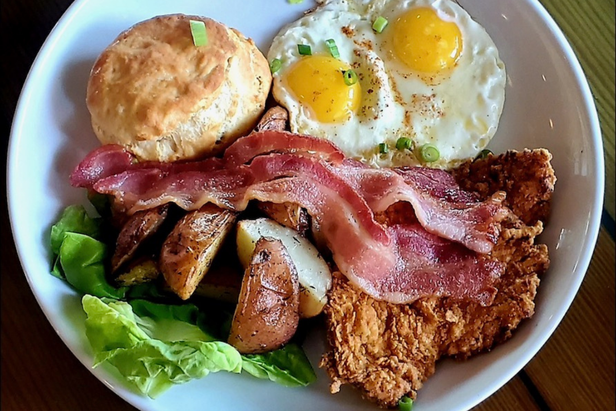 plate with fried chicken, eggs, bacon, potatoes and biscuit