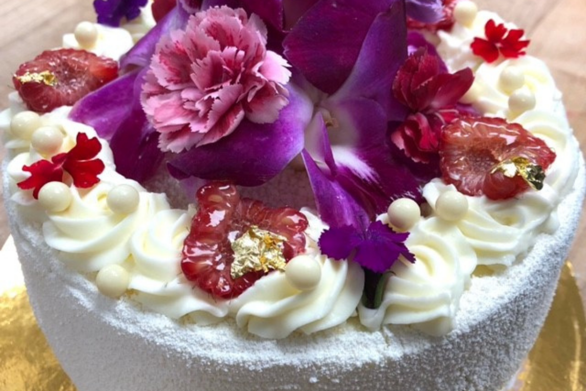 white cake with real purple and red flowers
