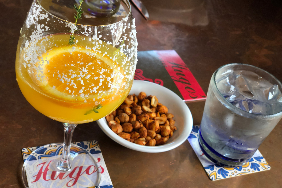 orange colored margarita and snack