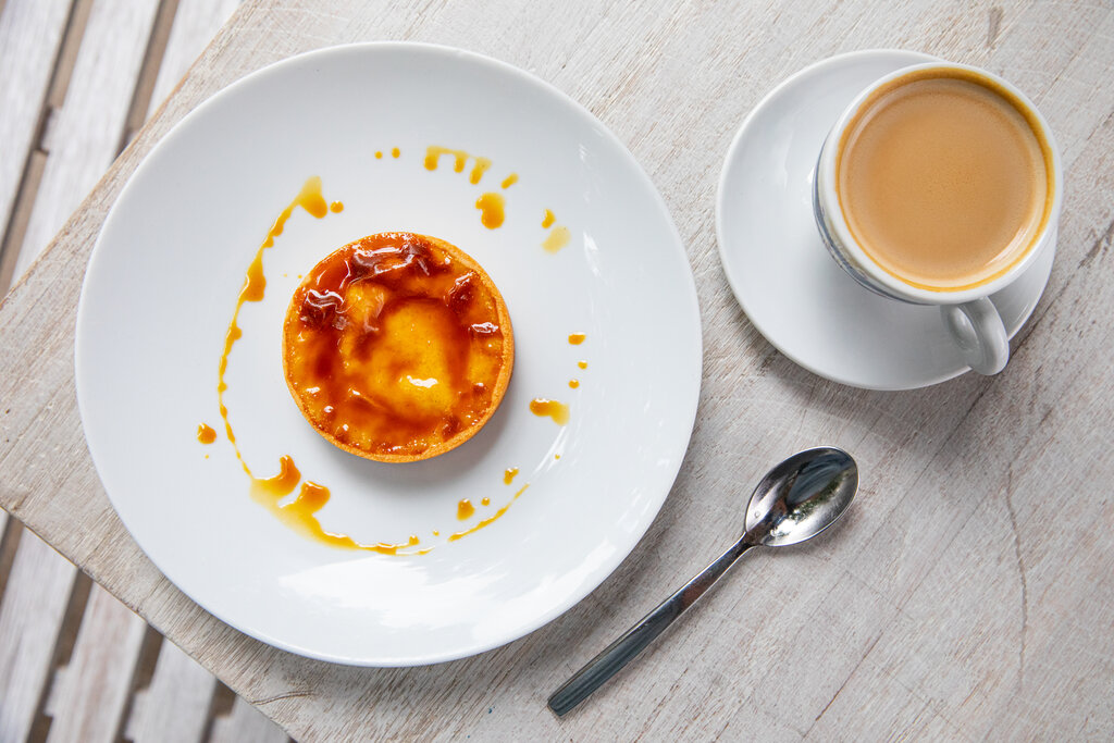 Photo of a custard tarte with caramel sauce drizzled around teh plate and a cup of coffee.