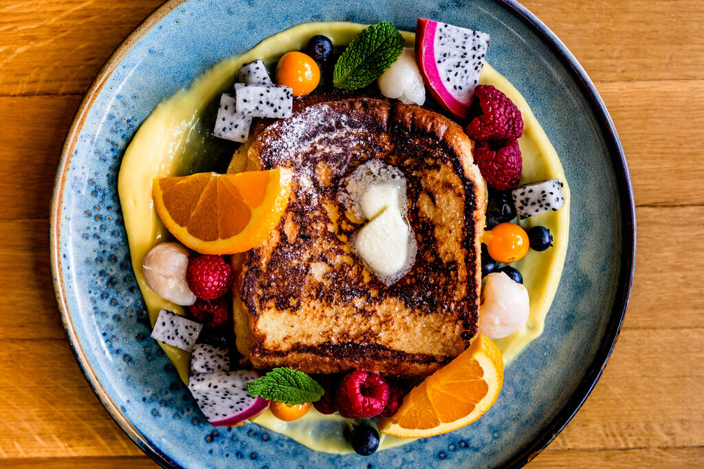 Photo of French toast on a plate with tropical fruit and oranges.