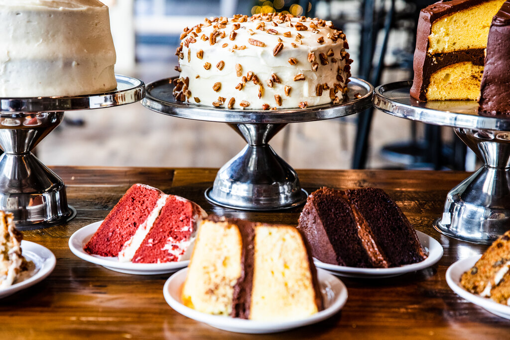 Picture of several cakes on cake stands and plates, including red velvet and yellow cake