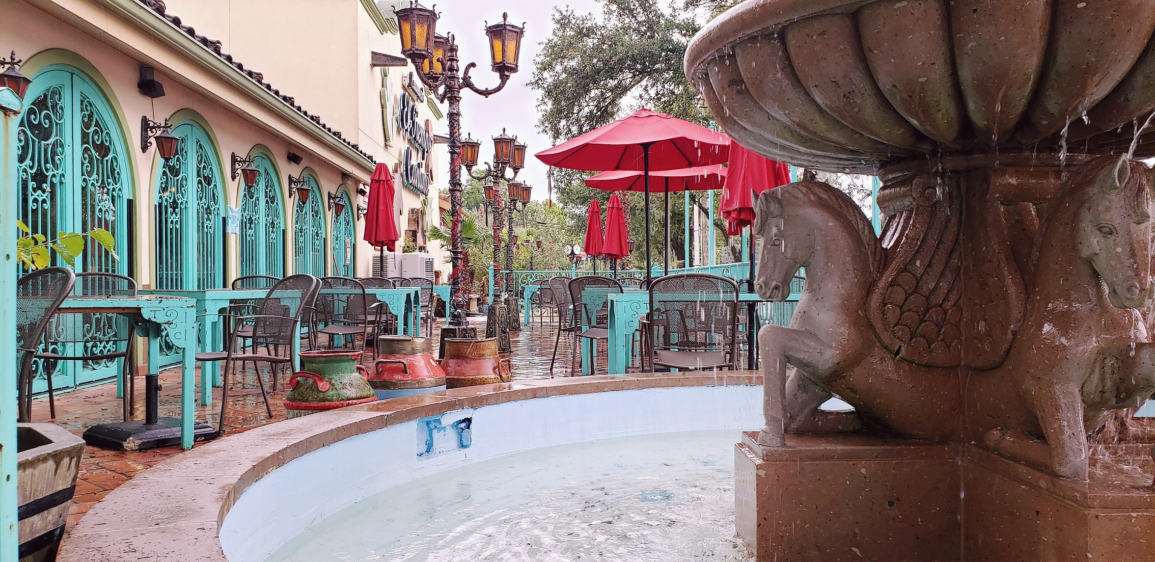 spacious patio with dining tables and large water fountain