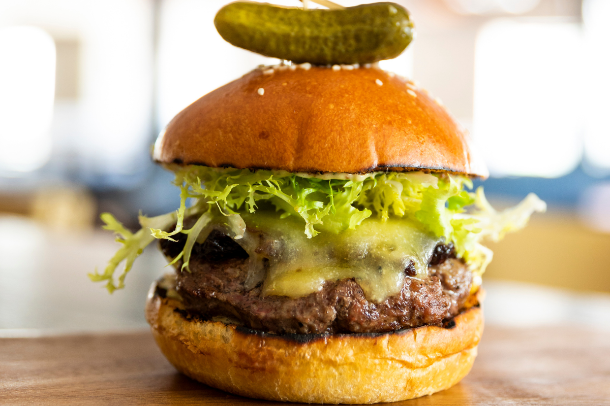 burger with cheese, lettuce and pickle on top