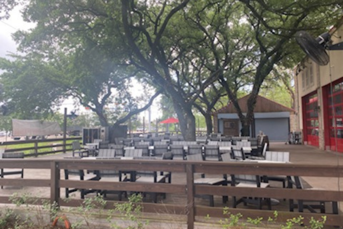 lage open patio with large live oak trees