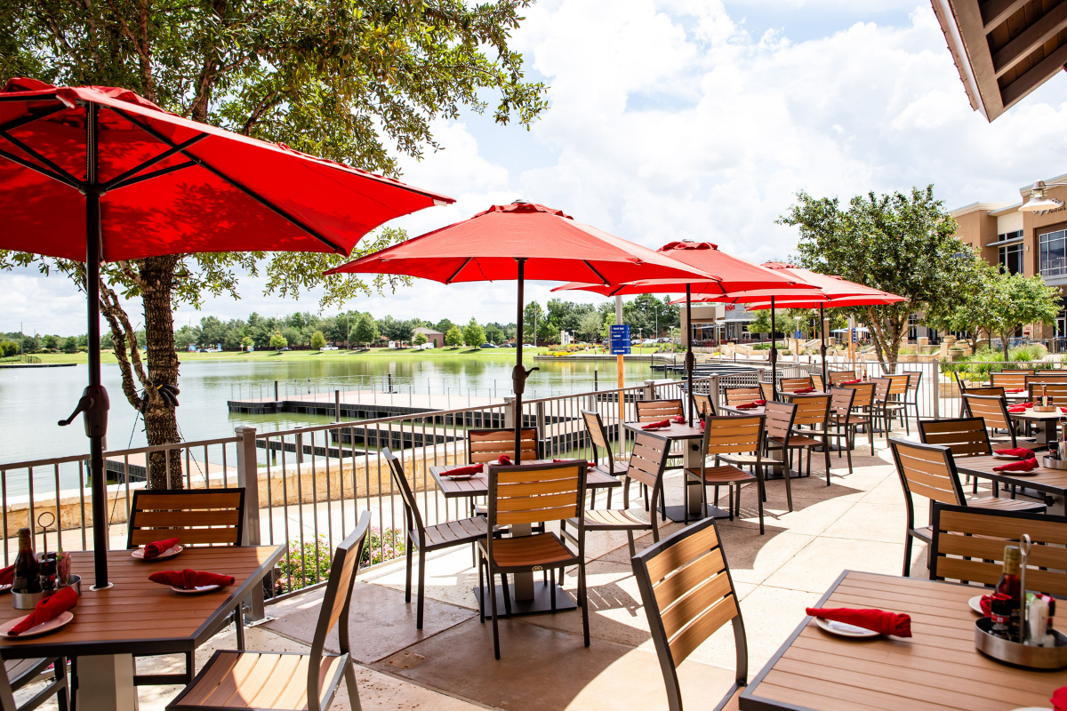 patio with outdoor dining and red umbrellas