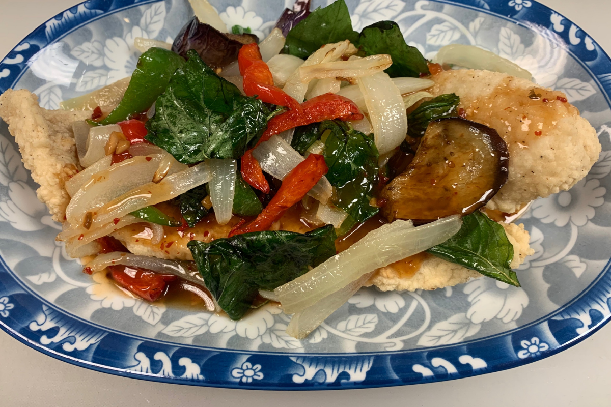 Plate of fried fish smothered in saucy stir fried vegetables