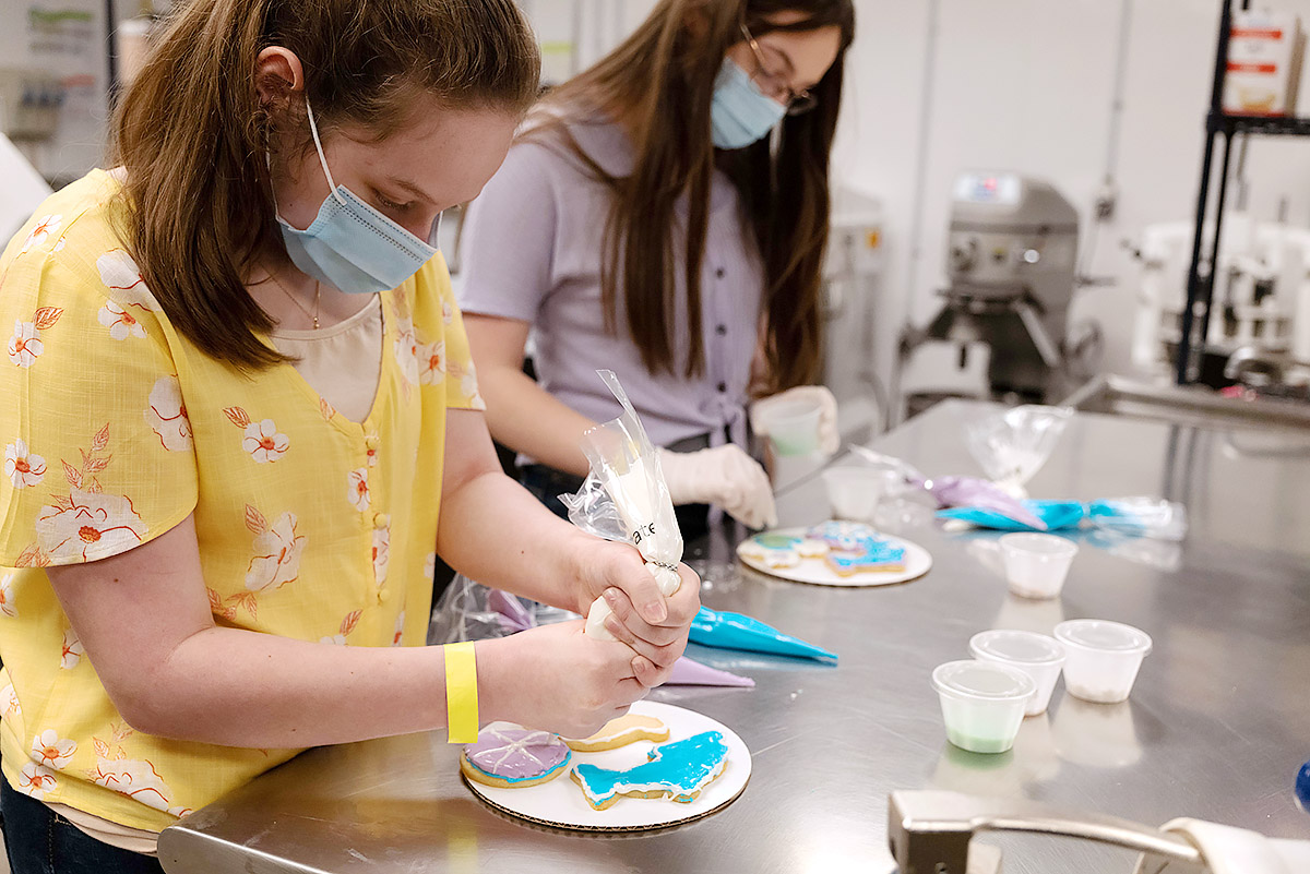 Two girls decorate cookies