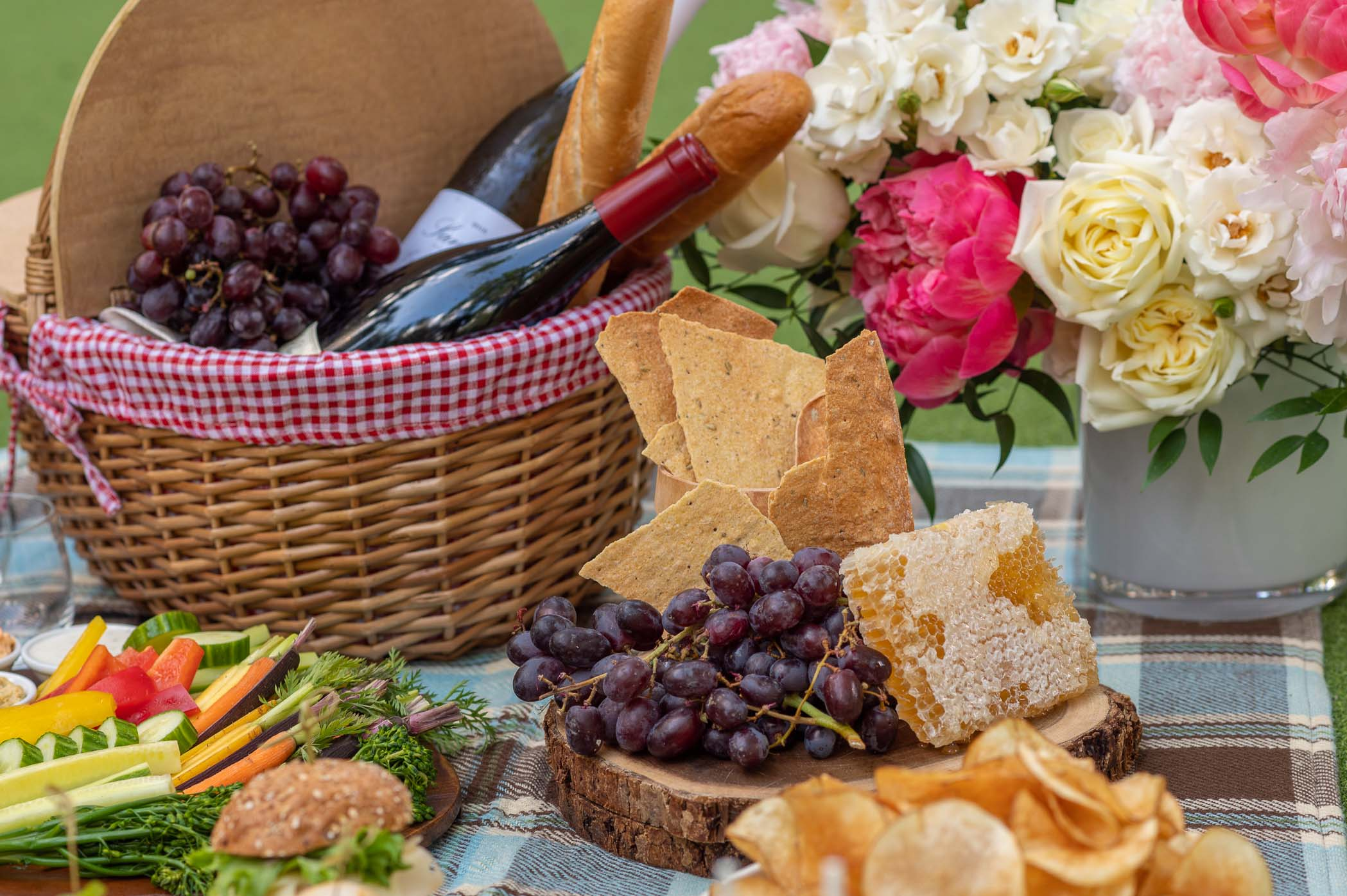 Picnic spread with basket and lots of food and wine