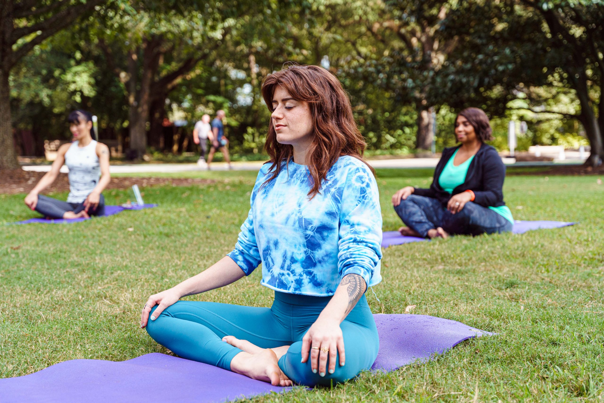 A girl in blue sitting on a yoga mat